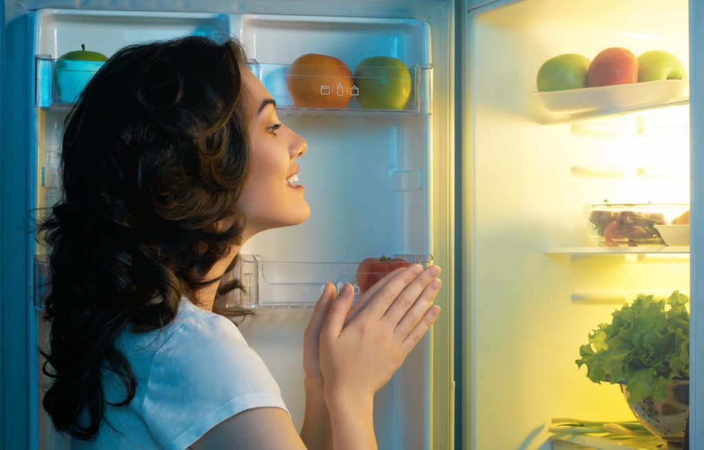 kvinde kigger ind i et koeleskab med frugt og groentsager 1024x654